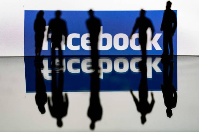 Silhuetas em frente ao logo do Facebook em Bruxelas