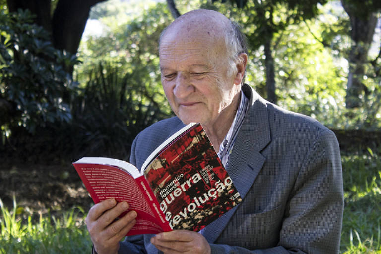 Homem idoso sentado lê um livro que mesmo escreveu sobre a Revolução Russa