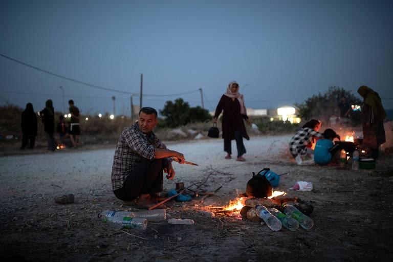 Homem em frente a fogueira ao anoitecer, ao fundo, uma mulher com lenço muçulmano na cabeça