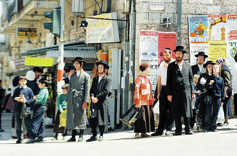 homens e crianças com trajes ortodoxos (cartolas e casacos longos), parados em uma esquina