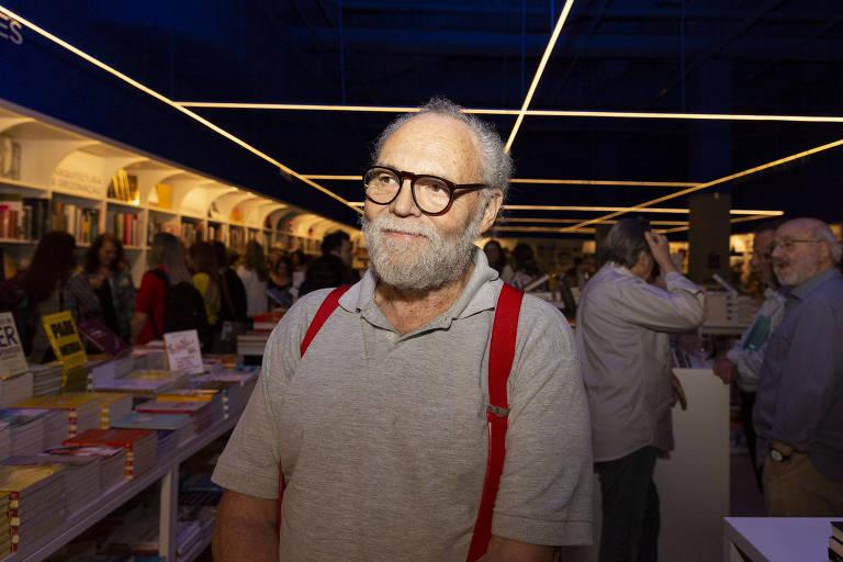 homem calvo de óculos usa camisa cinza e está em pé, sorrindo, me meio a várias estantes de livros
