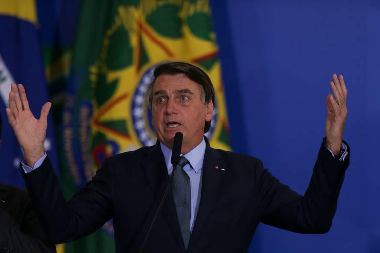 Na cerimônia, no Palácio do Planalto, Bolsonaro disse que escolas não deveriam ter sido fechadas durante a pandemia e que alguns governadores entraram em pânico por causa da mídia; Bolsonaro discursa tendo ao fundo uma bandeira, com as duas mãos para o alto
