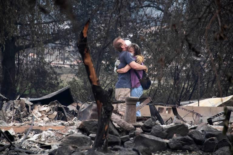 Casal se consola em meio às ruínas de sua casa destruída pelo fogo nos EUA; veja fotos de hoje
