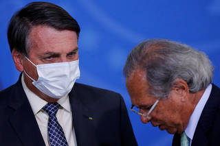 FILE PHOTO: Brazil's President Jair Bolsonaro talks with Brazil's Economy Minister Paulo Guedes during a ceremony to launch a program to expand access to credit at the Planalto Palace in Brasilia