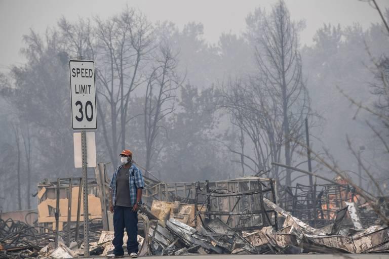 Homem passa por área atingida por incêndio e coberta de fumaça em Phoenix, no Oregon