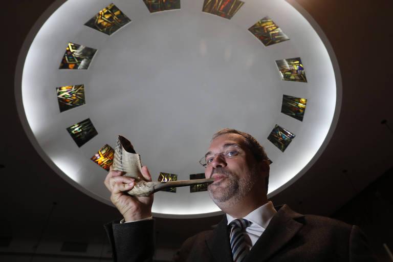 O rabino Michel Schlesinger com o shofar, em 2018; a foto o mostra retratado meio de baixo para cima, de modo que aparece uma espécie de cúpula no teto; ele segura o shofar, uma espécie de berrante pequeno, feito de chifre de carneiro, com a mão direita junto à boca, como se fosse tocá-lo