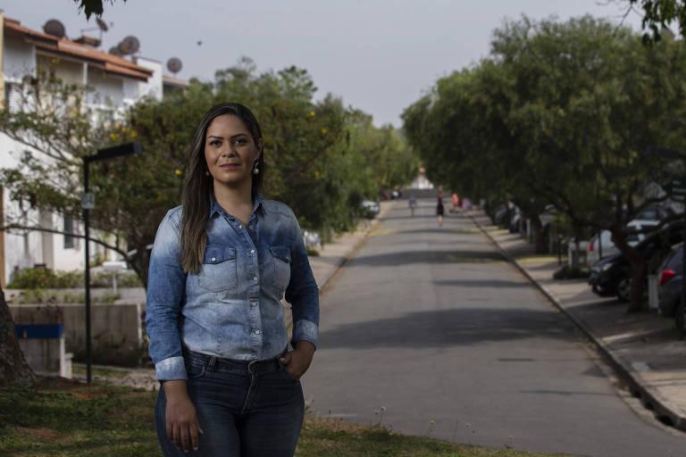 Em pé, mulher de cabelo comprido, blusa e calça com rua, árvores e casas ao fundo