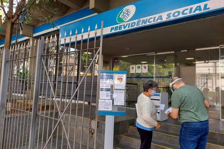 Foto mostra a fachada de uma agência da Previdência Social. Há um portão de barras cinzas e uma fachada em azul com o símbolo do INSS. Um homem e uma mulher, ambos idosos, conversam em frente à entrada.