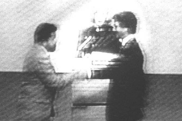 Homens dão as mãos em imagem borrada e em preto e branco