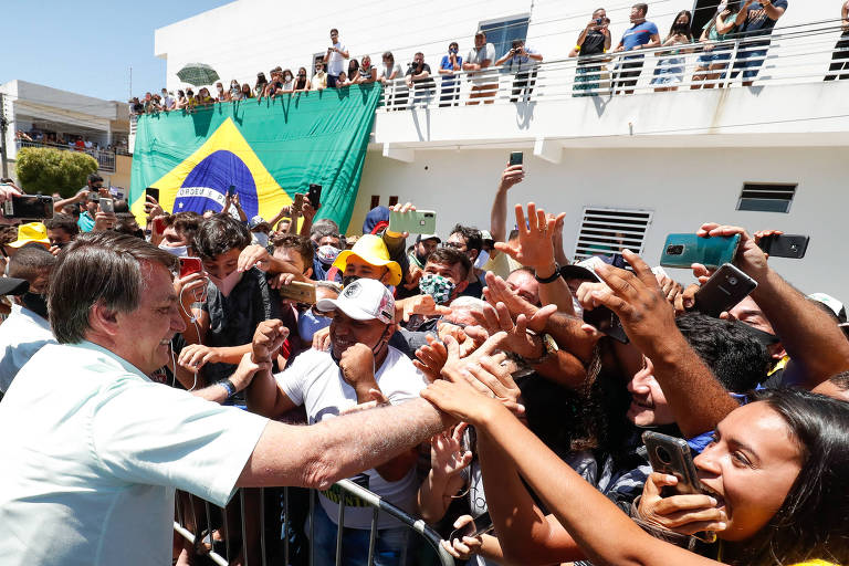Presidente Bolsonaro de camisa branca e sem máscara cumprimenta multidão de moradores.