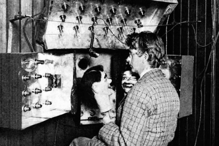 homem está sentado diante de uma série de refletores e tem fantoches em suas mãos