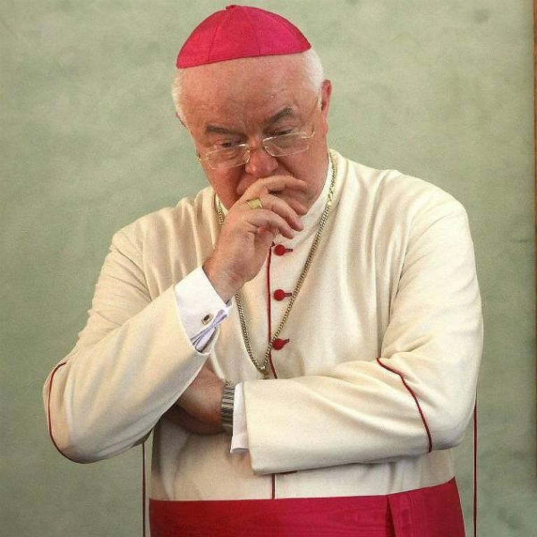 Homem idoso com roupa de padre, com touca vermelha