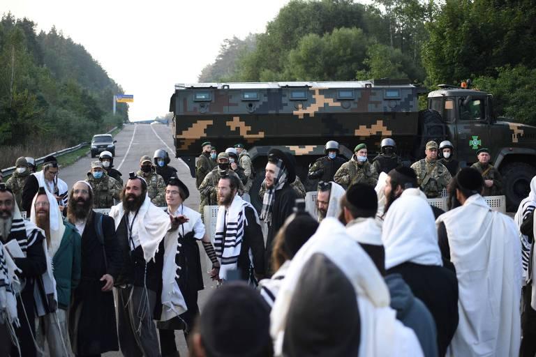 judeus ultraortodoxos aguardam em frente a guardas ucranianos