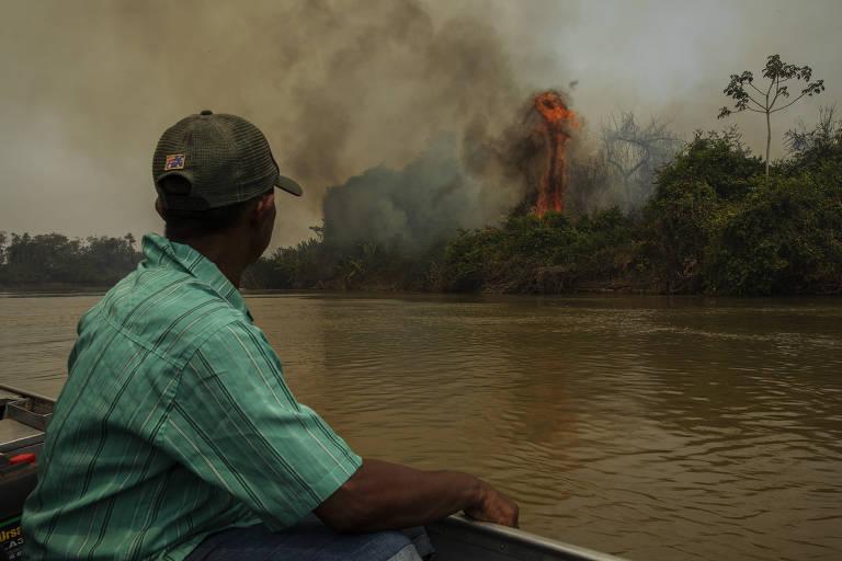 Guilherme Pedroso da Silva, 63, morador da Terra Indígena Baía dos Guató, no Pantanal de Mato Grosso, observa um incêndio florestal as margens do rio Cuiabá; ele está num barco e vê ao fundo a vegetação queimando