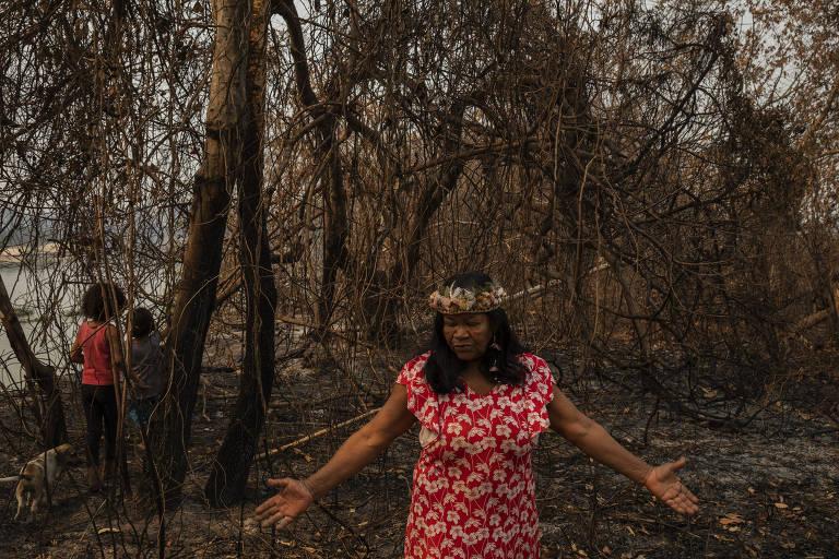 A liderança Sandra Guató mostra terreno queimado perto de sua casa na TI Baía dos Guató, que teve 83% de seu território consumido pelo fogo; no entorno de sua casa, salvou-se apenas uma pequena horta; ela usa um cocar baixo, com plumas formando flores, e um vestido vermelho estampado de flores brancas