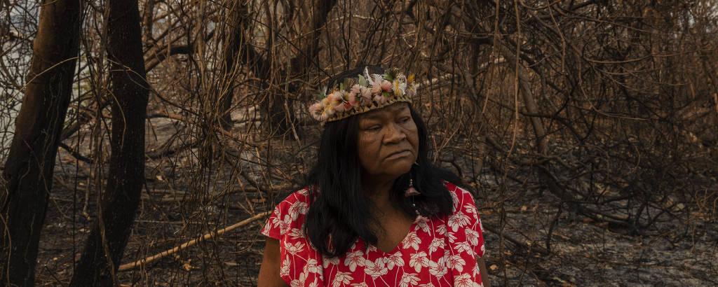 Sandra Guató, liderança da Terra Indígena Baia dos Guato, em meio à vegetação queimada; é uma mulher idosa, de cabelos negros, com um cocar que parece uma coroa de flores; ela usa um vestido vermelho estampado com flores brancas e tem um olhar desalentado em meio à vegetação totalmente seca e retorcida
