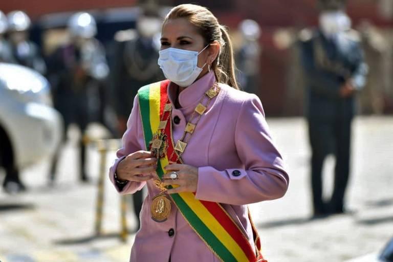 De máscara, faixa presidencial e casaco rosa, Añez caminha no sol