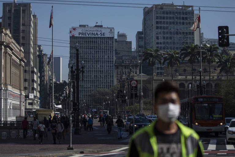 No primeiro plano, um homem negro de máscara caminha no sol, no centro de São Paulo. No fundo, um outdoor da prefeitura encoraja a população a se prevenir do novo coronavírus.