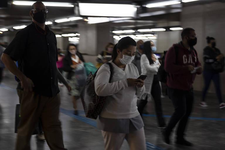 Pessoas de máscara andam em corredor do metrô. No centro, uma mulher de branco olha para a tela do celular e carrega uma mochila. Uma exposição mais longa mostra o movimento das pessoas, que aparecem meio borradas.