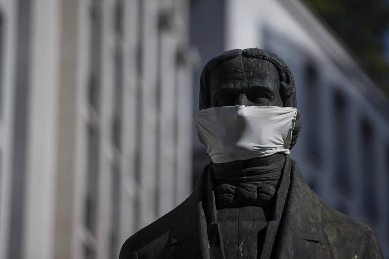Em primeiro plano, busto de estátua com luz do sol lateral. A estátua veste uma máscara de pano branco. No fundo, a fachada da prefeitura de São Paulo.