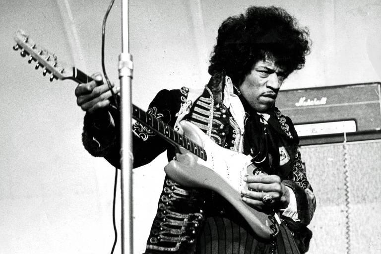 Homem negro com cabelo black power toca guitarra
