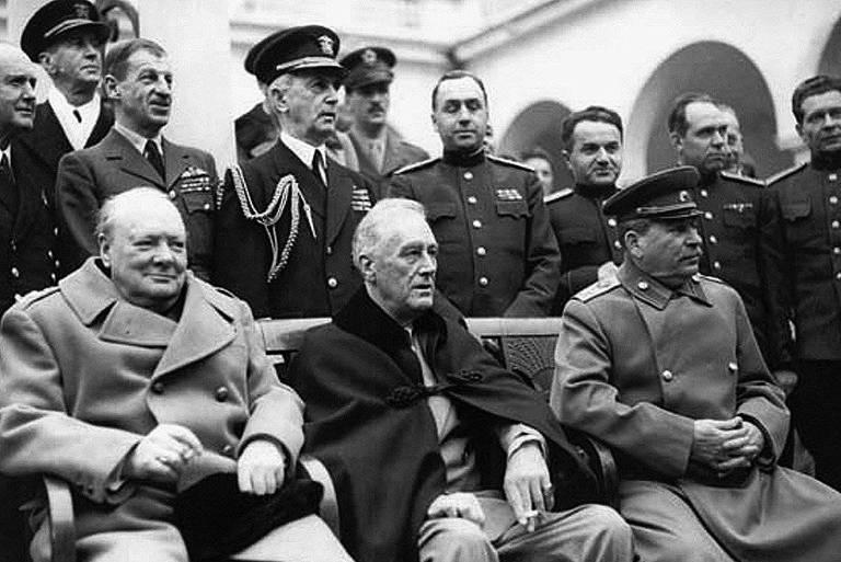 Homens sentados na frente de soldados