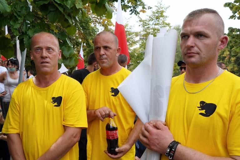 três homens de camiseta amarela segurando bandeiras
