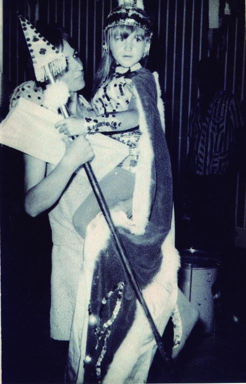 Menina com roupa de princesa sentada no colo de uma  mulher