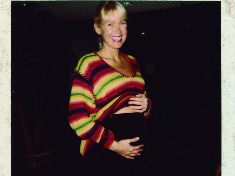 Mulher com blusa colorida acaricia barriga e sorri
