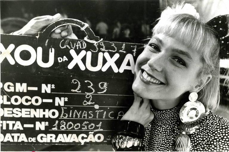 "Mulher segura placa escrito ""xou da xuxa"""