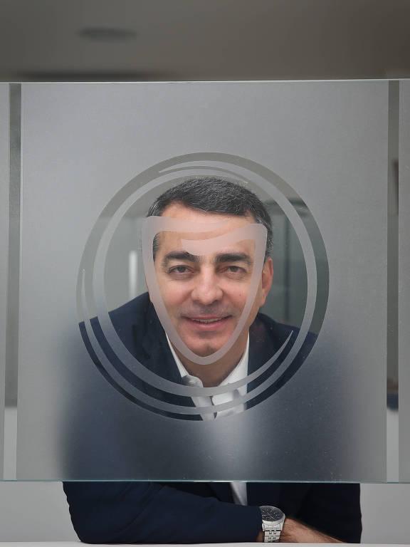 Homem olha para a câmera através de vidro com desenho de dente estilizado