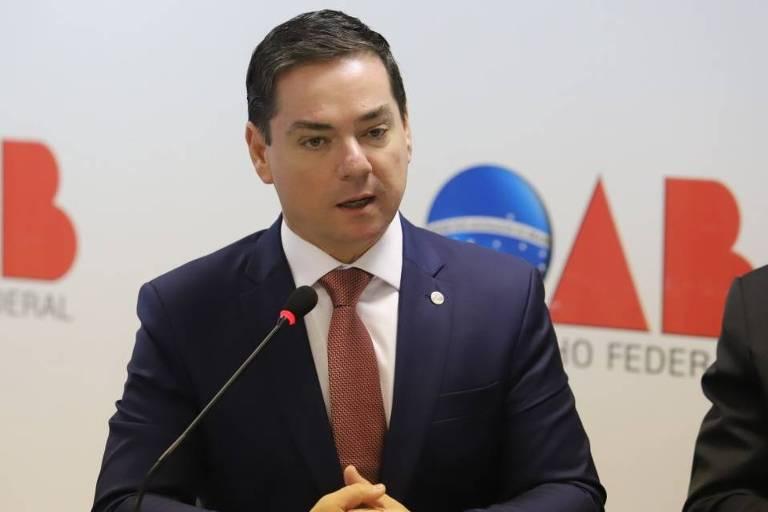 Homem branco de terno e gravata, sentado à bancada e falando ao microfone. Ao fundo logo da do Conselho Federal da OAB