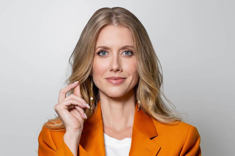 Mulher branca, loira, veste terno laranja, está de pé e tem um dos braços cruzados, sorri levemente