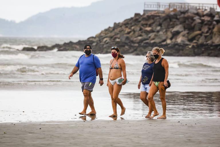 Um homem e três mulheres caminham de máscara e roupa de banho na praia