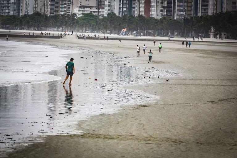 Homem caminha na beira do mar, com pessoas ao fundo na praia, em Santos