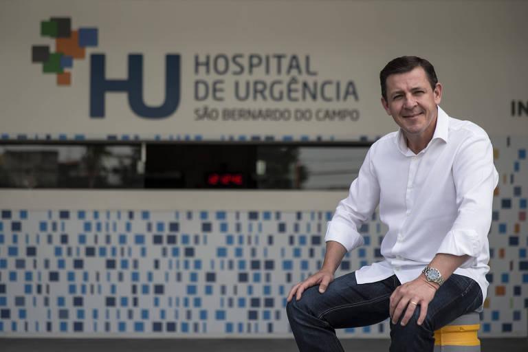 Morando sentado num banquinho. Atrás dele, ladrilhos azuis e o letreiro do hospital acima de um balcão de atendimento