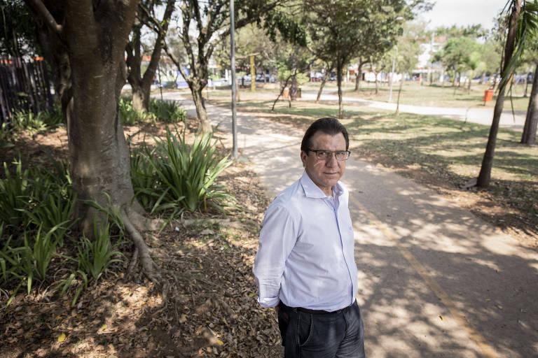 Um homem de camisa branca e óculos no meio de uma praça, com várias árvores e um caminho ao fundo