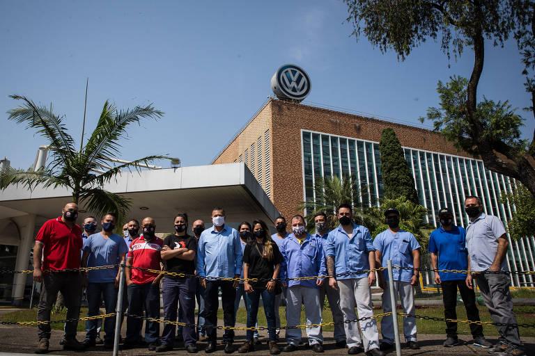 Grupo de pessoas diante de uma fábrica