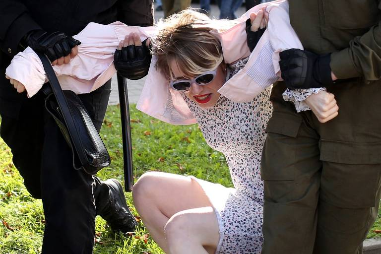 Moça de vestido branco e óculos escuros é arrastada pelos braços por dois policiais, um de cada lado