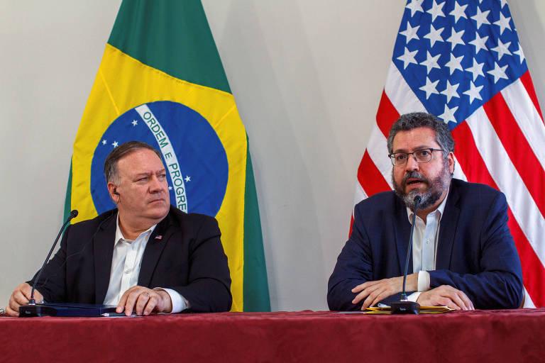 estão sentados atrás de uma mesa. Ao fundo, as bandeiras do Brasil e dos Estados Unidos estão penduradas