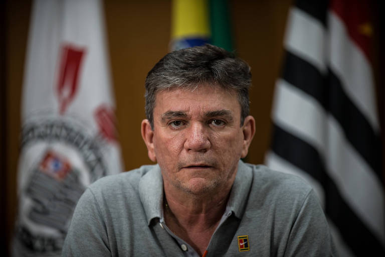Homem olhando sério para a câmera, com bandeira do Corinthians atrás dele