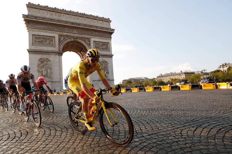 Ciclista de amarelo, com outros ciclistas atrás dele, passa pelo Arco do Triunfo