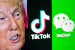 A picture of U.S. President Donald Trump is seen on a smartphone in front of displayed Tik Tok and WeChat logos in this illustration