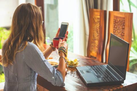 Mulher usando celular e laptop dentro de casa e bebendo café / chá. Foto: astrosystem / Adobe stock