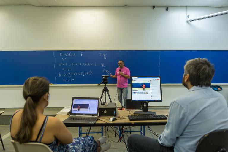 Lousa azul, professor dá aula e outras duas pessoas sentadas gravam ele falando com uma câmera