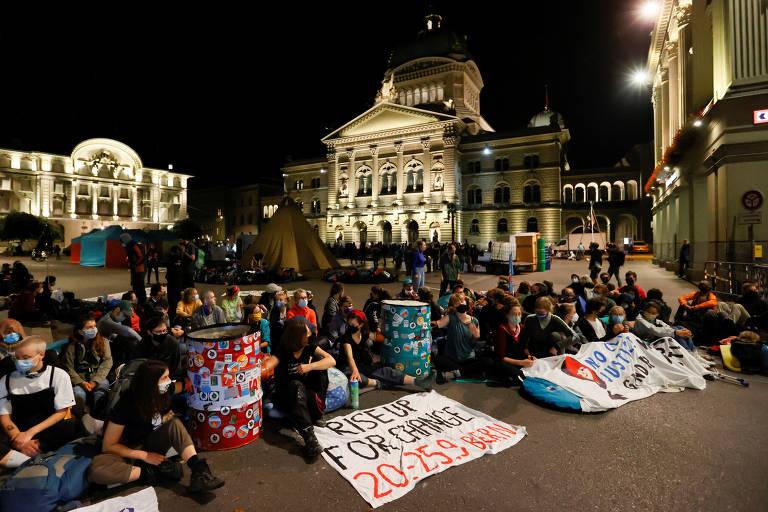 Ativistas sentados em praça em frente a prédio histórico
