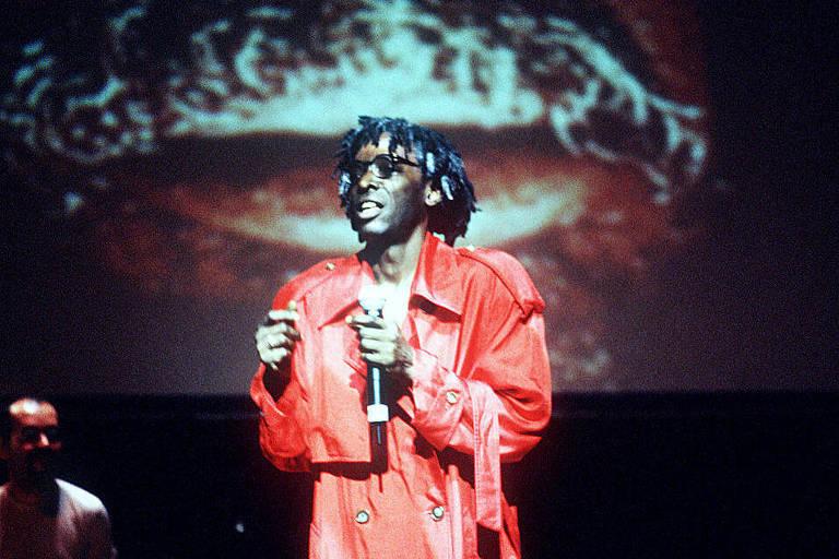 Homem com terno vermelho dança no palco