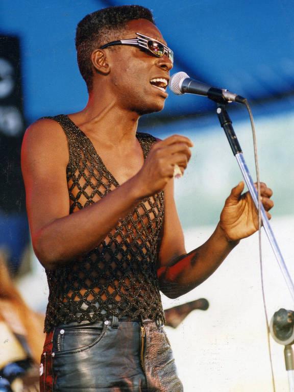 Homem com blusa quadriculada preta e calça de couro canta