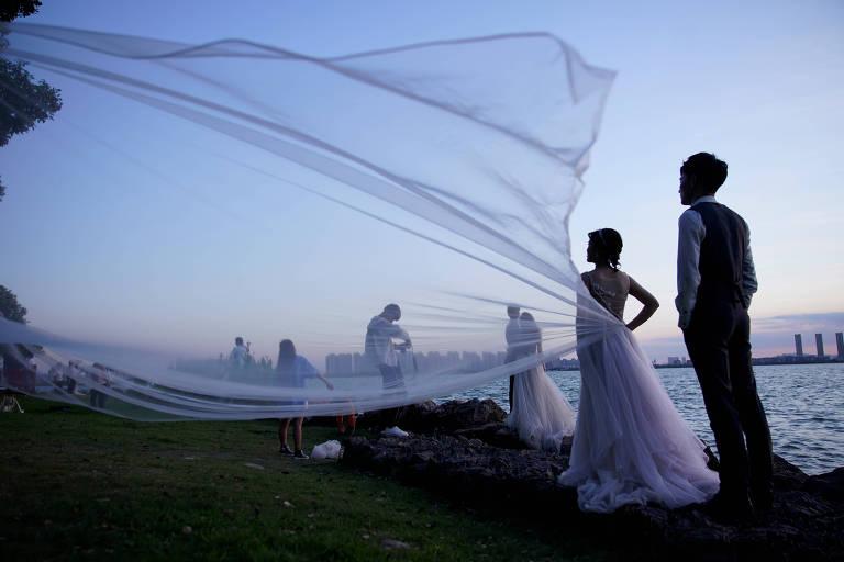 Um casal de noivos posam para uma sessão de foto na beira de um lago, na luz do crepúsculo. Um pedaço de tecido transparente do vestido da noiva voa no ar. Atrás deles, há vários casais de noivos posando para fotógrafos.