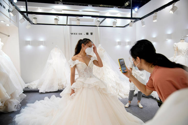 Uma modelo usando um vestido de noiva e uma máscara branca posa para uma mulher que tira uma fotografia de celular, no meio de uma sala de exposição de vestidos.